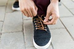 Fermez-vous des mains masculines attachant des dentelles de chaussure sur la rue Photographie stock