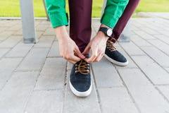 Fermez-vous des mains masculines attachant des dentelles de chaussure sur la rue Photo stock