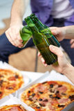 Fermez-vous des mains masculines avec de la bière et la pizza à la maison Images stock