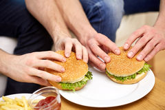 Fermez-vous des mains masculines avec des hamburgers sur la table Images libres de droits