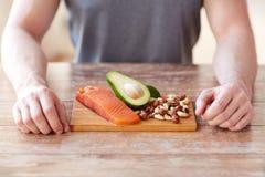 Fermez-vous des mains masculines avec des riches de nourriture en protéine images libres de droits