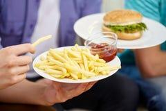 Fermez-vous des mains masculines avec les aliments de préparation rapide des plats Image libre de droits