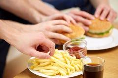 Fermez-vous des mains masculines avec les aliments de préparation rapide sur la table Photographie stock