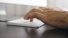 Fermez-vous des mains masculines dactylographiant sur le clavier dans le bureau clips vidéos