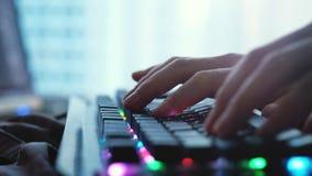 Fermez-vous des mains masculines dactylographiant sur un clavier d'ordinateur portable par la fenêtre panoramique photos libres de droits
