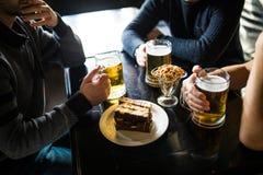 Fermez-vous des mains masculines faisant tinter des verres de bière à la barre ou au bar Images stock