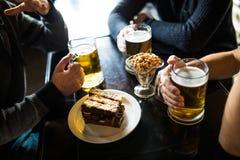 Fermez-vous des mains masculines faisant tinter des verres de bière à la barre ou au bar Image stock