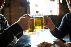Fermez-vous des mains masculines faisant tinter des verres de bière à la barre ou au bar Photo libre de droits