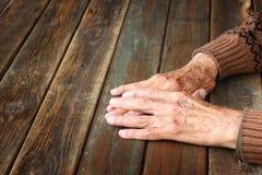 Fermez-vous des mains masculines pluses âgé sur la table en bois Photo stock
