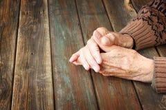 Fermez-vous des mains masculines pluses âgé sur la table en bois Image libre de droits