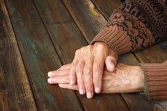 Fermez-vous des mains masculines pluses âgé sur la table en bois Image stock