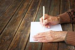 Fermez-vous des mains masculines pluses âgé sur la table en bois. inscription sur le papier blanc Photographie stock libre de droits