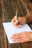 Fermez-vous des mains masculines pluses âgé sur la table en bois. inscription sur le papier blanc Photographie stock