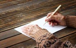 Fermez-vous des mains masculines pluses âgé sur la table en bois. inscription sur le papier blanc Image libre de droits