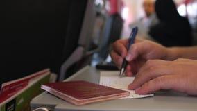 Fermez-vous des mains masculines que le passager avec le passeport complète les cartes de migration ou d'arrivée dans le vol plat banque de vidéos