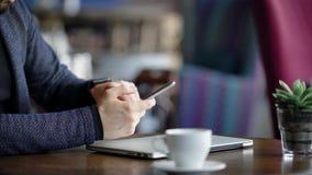 Fermez-vous des mains masculines tenant le smartphone et introduisant le message Jeune homme d'affaires s'asseyant à la table ave clips vidéos
