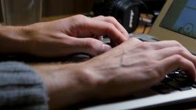 Fermez-vous des mains masculines utilisant l'ordinateur portable au bureau, mains du ` s d'homme dactylographiant sur le clavier  Image libre de droits