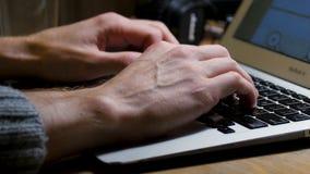 Fermez-vous des mains masculines utilisant l'ordinateur portable au bureau, mains du ` s d'homme dactylographiant sur le clavier  Photos libres de droits