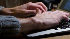 Fermez-vous des mains masculines utilisant l'ordinateur portable au bureau, mains du ` s d'homme dactylographiant sur le clavier  banque de vidéos