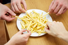 Fermez-vous des mains prenant des pommes frites de plat Image stock