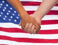 Fermez-vous des mains se tenant au-dessus du drapeau américain Image stock