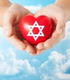 Fermez-vous des mains tenant le coeur avec l'étoile juive Photos stock