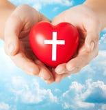 Fermez-vous des mains tenant le coeur avec le symbole croisé Image stock