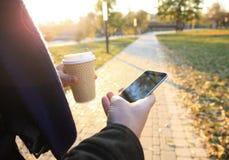 Fermez-vous des mains utilisant le téléphone intelligent moderne, jour ensoleillé, lumière du soleil, elle causant avec des amis  Photo libre de droits