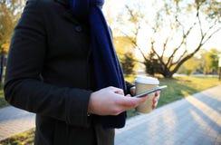 Fermez-vous des mains utilisant le téléphone intelligent moderne, jour ensoleillé, lumière du soleil, elle causant avec des amis  Photos libres de droits
