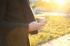 Fermez-vous des mains utilisant le téléphone intelligent moderne, jour ensoleillé, lumière du soleil, elle causant avec des amis  Photographie stock