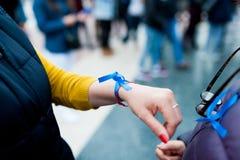 Fermez-vous des mains vénézuéliennes de femme portant le ruban bleu à l'appui du Président Juan Guaido pendant la tentative de co images stock