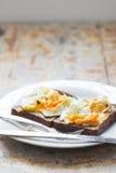 Fermez-vous des oeufs pochés écrasés sur une table de cuisine rustique photo stock