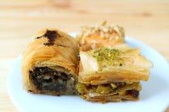 Fermez-vous des pâtisseries de baklava dans différentes saveurs du plat blanc servi sur le Tableau en bois photos stock