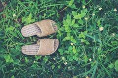 Fermez-vous des pantoufles sur le fond d'herbe, concept de relaxation image stock