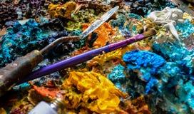 Fermez-vous des peintures à l'huile et des brosses sur la palette images stock