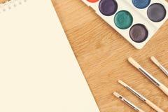 Fermez-vous des peintures d'aquarelle, des brosses et de la feuille vide de livre blanc sur le fond en bois Photographie stock