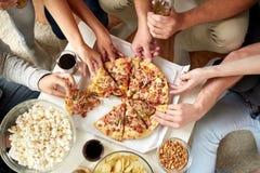 Fermez-vous des personnes prenant des tranches de pizza à la maison Images stock