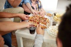 Fermez-vous des personnes prenant des tranches de pizza à la maison Photos libres de droits