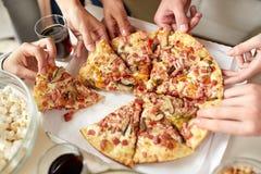 Fermez-vous des personnes prenant des tranches de pizza de boîte Images stock