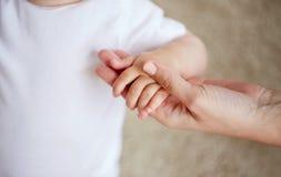 Fermez-vous des petites mains de bébé et de mère Image libre de droits