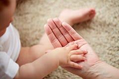Fermez-vous des petites mains de bébé et de mère Photos libres de droits