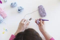 Fermez-vous des petits chaussons de tricotage d'une femme pour un bébé Photos libres de droits