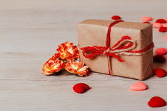 Fermez-vous des petits coeurs lumineux, des fleurs de ressort et de la corde enveloppée par cadeau de métier sur le fond en bois Images stock