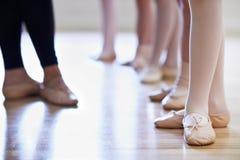 Fermez-vous des pieds d'And Children de professeur dans la classe de danse de ballet Images libres de droits