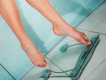 Fermez-vous des pieds de femme pesant dans la salle de bains Photographie stock