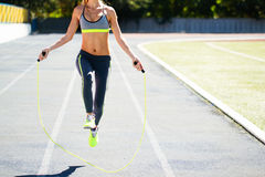 Fermez-vous des pieds de femme sautant, utilisant la corde à sauter dans le stade Images stock