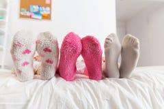 Fermez-vous des pieds de femmes dans les chaussettes sur le lit à la maison Photographie stock libre de droits