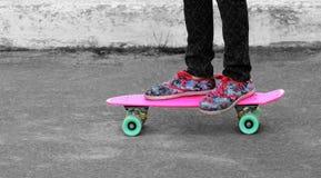 Fermez-vous des pieds du ` s de fille dans des espadrilles florales se tenant sur le panneau rose de penny Photos stock
