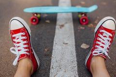 Fermez-vous des pieds et du panneau bleu de patin de penny avec les roues roses Photos libres de droits