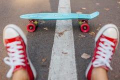 Fermez-vous des pieds et du panneau bleu de patin de penny avec les roues roses Image libre de droits